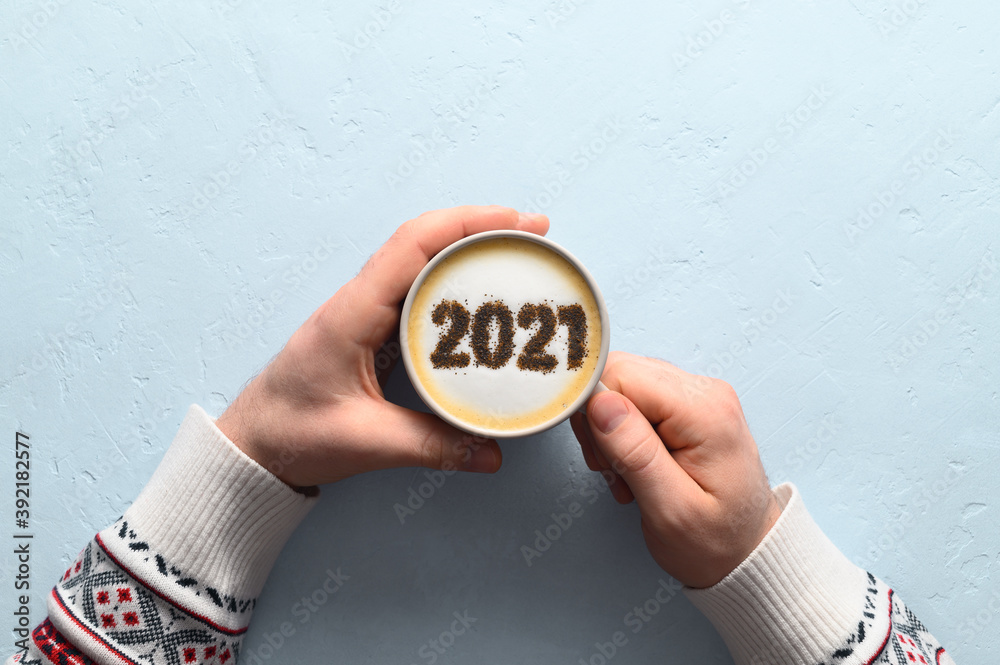 Fototapeta New year background. Male hands hold coffee cup with number 2021 on frothy surface of cappuccino. Pastel blue background. Food creative concept. Top view, copy space