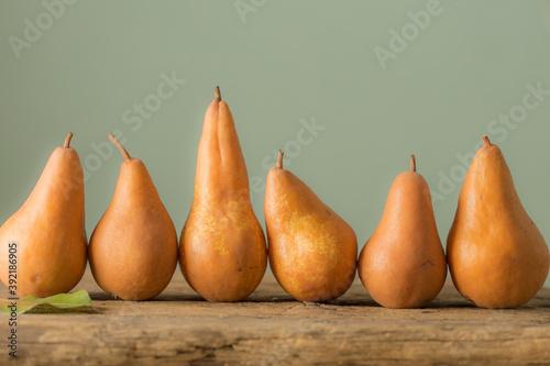 Fotografie, Obraz Ripe orange pears on a wooden rustic desk in a row