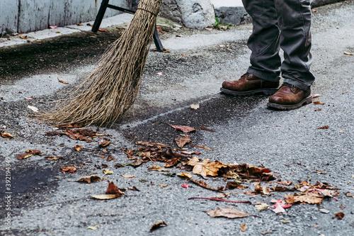 Photo Homme en train de passer le balai devant sa porte et enlever les feuilles mortes