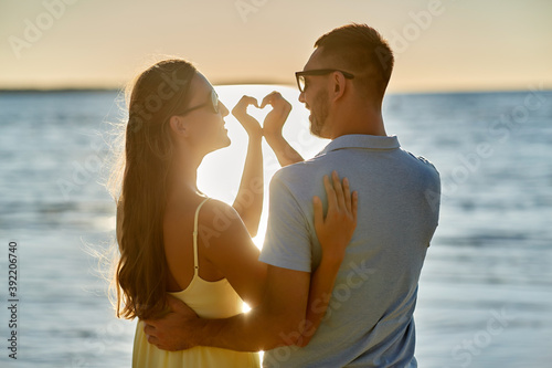 leisure, relationships and people concept - happy couple in sunglasses hugging a Canvas Print