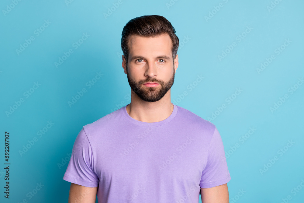 Fototapeta Portrait of young handsome serious reliable male look camera wear violet t-shirt isolated on blue color background