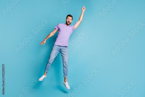 Fotografering Full length body size photo of jumping man pretending superhero flying amazed in