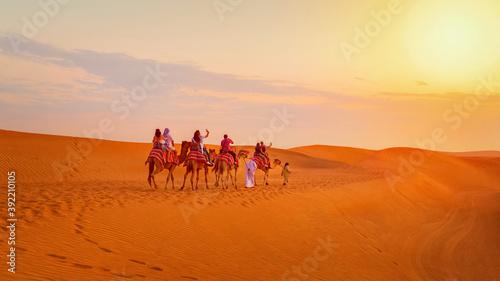Foto Caravan with group of tourists riding camels through Dubai desert during safari