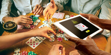 Online Gambling, Casino Concept. Hand Holding Device With Lottery, Casino Cover. Playing Dips And Cards On Table On The Background. Poker, Bookmaking, Gaming, Modern Technologies, Business And Finance
