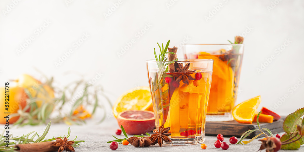 Fototapeta Winter or autumn hot healing tea with pear, orange, lingonberries, sea buckthorn and spices in glass cup.