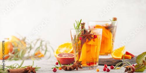 Winter or autumn hot healing tea with pear, orange, lingonberries, sea buckthorn and spices in glass cup.