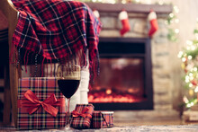Woman Legs In A Socks Covered Plaid Sitting And Relaxation On Armchair Near Fareplace And Christmas Tree With Glass Of Wine After Finishing Pakking Gift Boxes For Family. Bottom View.