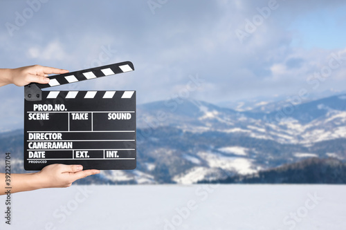 Valokuvatapetti Assistant holding clapperboard outdoors, closeup