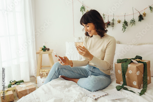 Canvastavla Woman enjoying wine sitting on bed and doing a video call