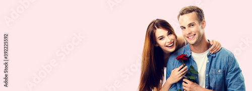 Portrait image - happy hugging couple with flower, with copy space for slogan or text, isolated over pink background. Love, relationship, dating, flirting, lovers, romantic studio concept.