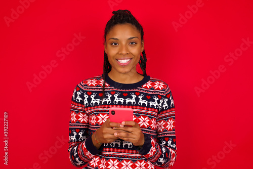 Cuadros en Lienzo Young beautiful African American woman standing against red background enjoys di