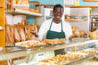 Smiling African American man working in small bakery, offering appetizing freshly baked bread and pastry