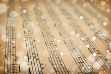 Old Sheet With Christmas Music Notes As Background, Snowflakes And Bokeh Effect