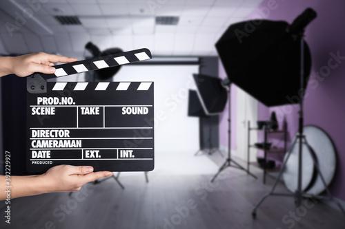 Obraz na plátně Assistant holding clapperboard on filming location, closeup