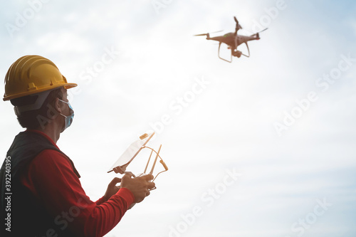 Vászonkép Man pilot engineer flying with drone while wearing protective mask during corona