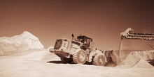 Front End Loader Near The Stone Crushing Equipment At The Limestone Quarry, Monochrome Panoramic Image Of A Light Brown Color, Sepia. Mining Industry.