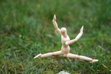 Wooden Mannequin Jumping On Grass