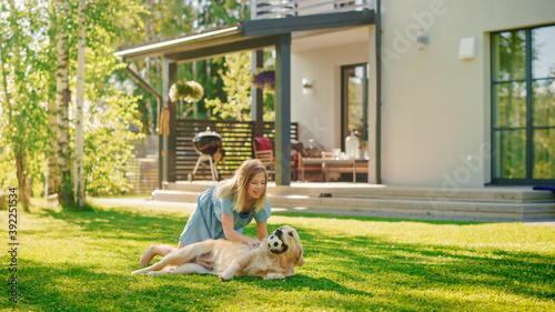 Fotografie, Obraz Cute Girl Has fun with Happy Golden Retriever Dog on the Backyard Lawn