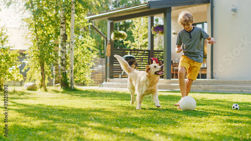 Foto Handsome Young Boy Plays Soccer with Happy Golden Retriever Dog at the Backyard Lawn