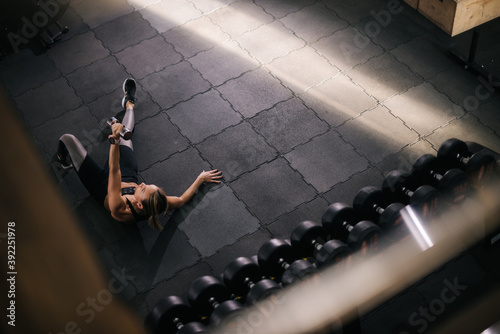 Slika na platnu Top down view of strong young woman with perfect athletic body lying on floor working out lifting dumbbell during sport workout training at modern fitness gym with dark interior