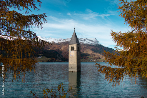 Famous submerged church steeple arising from the alpine Resia Lake, in the town of Curon Venosta, in the italian Dolomite region of Trentino Alto Adige Fototapet