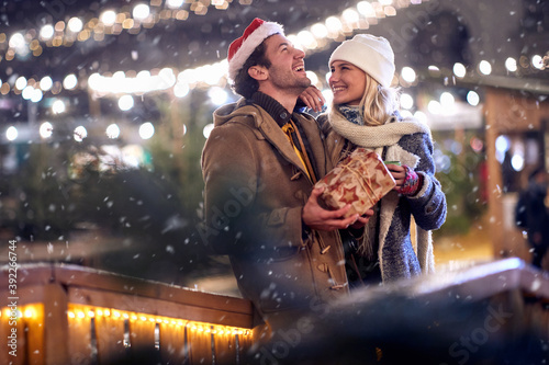 Happy moments of young couple in love at christmas festival in the city. Festival, love, relationship, Xmas, snow
