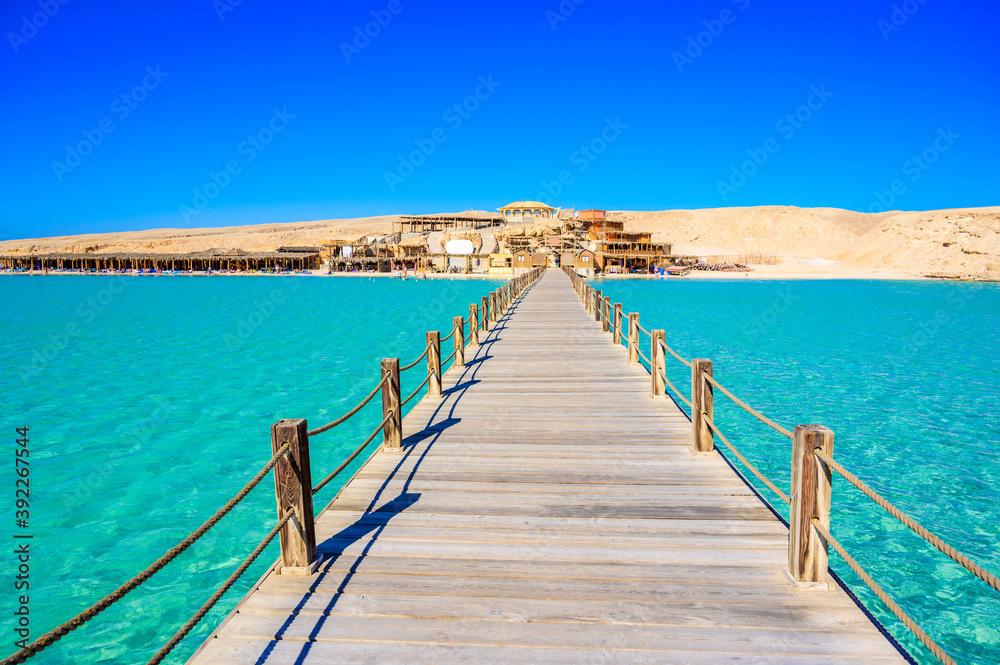 Fototapeta Wooden Pier at Orange Bay Beach with crystal clear azure water and white beach - paradise coastline of Giftun island, Mahmya, Hurghada, Red Sea, Egypt.