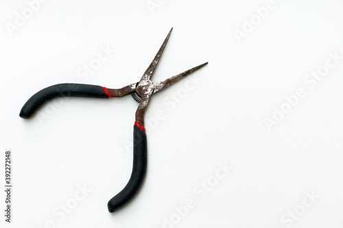 Old and rustic long nose cutting plier with black and red handle on white background Canvas Print