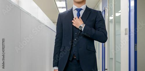 Fotografiet オフィスの廊下を歩きながら、ネクタイに手をあてるビジネスマン