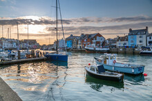 View Of Boats In The Old Harbour And Quayside Houses At Sunset, Weymouth, Dorset