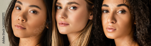 Obraz young multicultural models looking at camera isolated on white, banner - fototapety do salonu