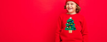Cute Blond Boy In Warm Hat And Christmas Sweater On Red Background With Smile On His Face