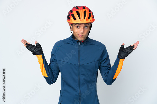 Slika na platnu Young cyclist Brazilian man isolated on white background having doubts while rai