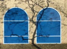 Shadow Of A Tree On Two Blue Arched Windows