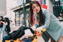 Stylish Woman Pushing Shopping Cart On Street