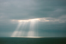 Sunlight Streaming Through A Cloudy Sky Onto The Ocean