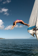 Woman Jumping To The Water From A Sailboat