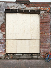 Big Gap In Old Brick Wall ,closed With Wooden Panels
