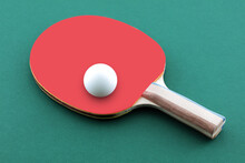 Green Ping Pong Table With Ball Resting On A Table Tennis Bat Paddle