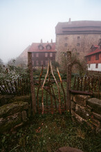 Mystical Scenery Of Abandoned Yard With Rusty Fence Against Old Brick Building Among Fog