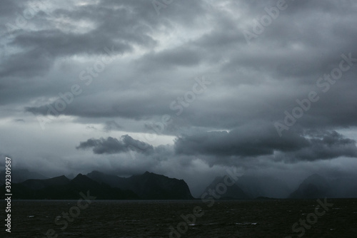 Scenic landscape of heavy clouds and silhouettes of mountains