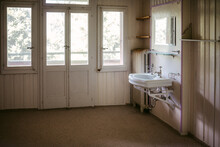 Interior Of Empty Bathroom With Wooden Walls In Abandoned House