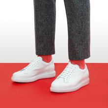 A Man In White Sneakers Stands On A Red Background.