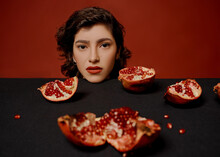 A Beautiful Young Woman In A Black Jacket Is Sitting At A Table On A Red Background. Holds Halves And Pieces Of Pomegranate Fruit