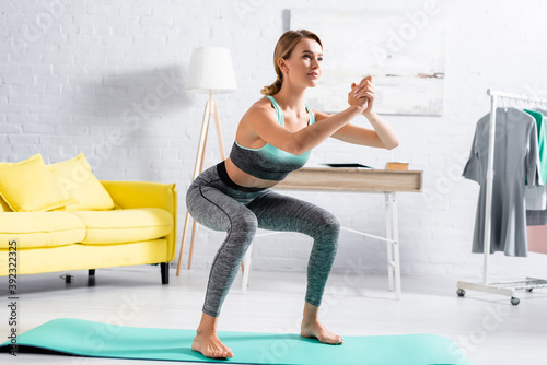 Canvastavla Barefoot sportswoman doing squat while training on fitness mat at home