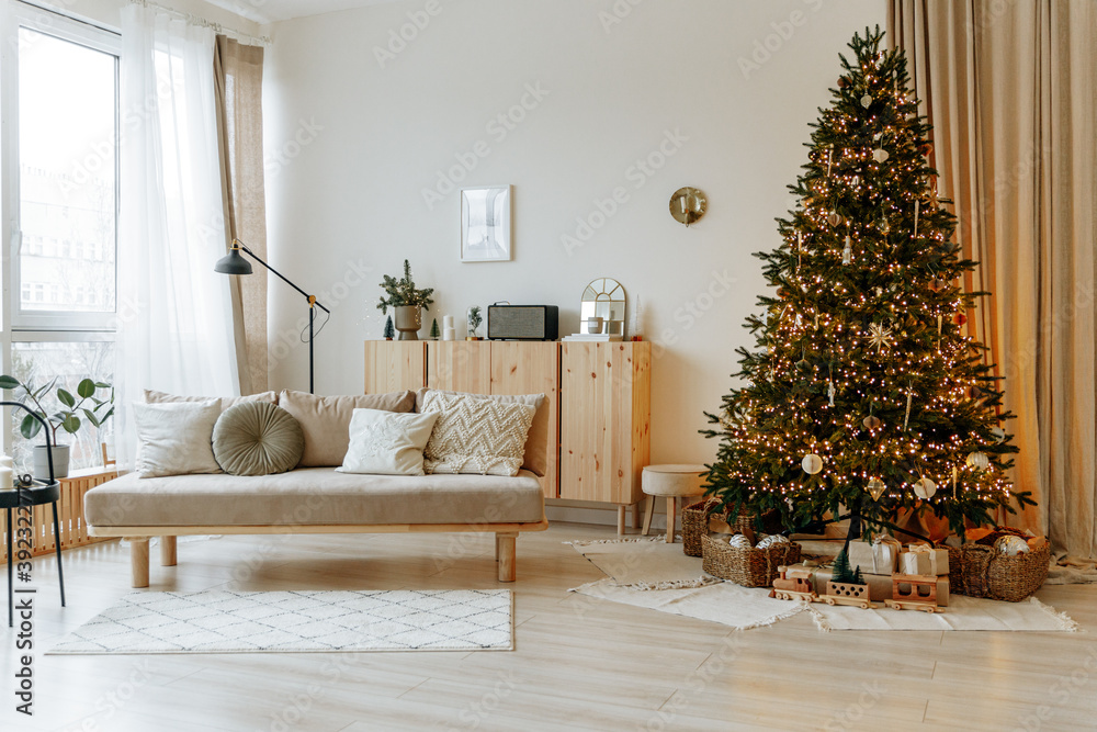 Fototapeta Bright interior of the living room with a sofa and a large Christmas tree. New year's interior.