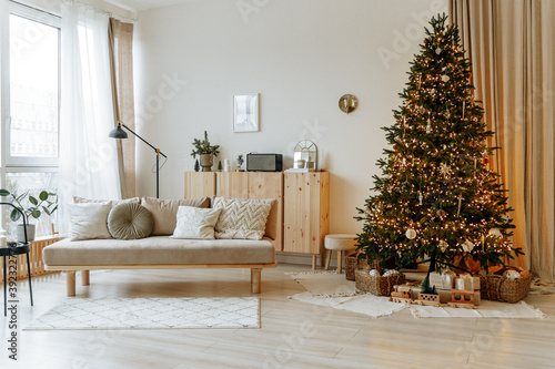 Foto Bright interior of the living room with a sofa and a large Christmas tree