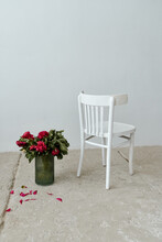 Still Life On A Concrete Floor With A White Retro Chair And A Bouquet Of Pink Fuchsia Peonies