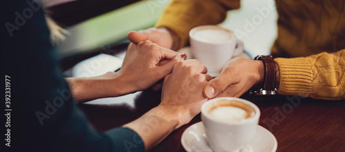 romantic couple holding hands at coffee shop Fotobehang