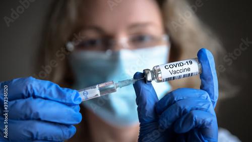 COVID-19 coronavirus vaccine, bottle and syringe in doctor hands Fototapeta